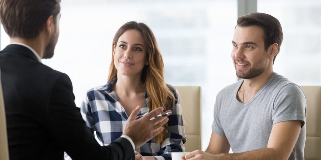 real estate agent talking to clients in office