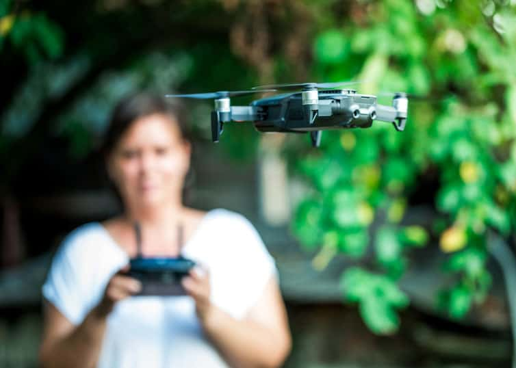 Woman operating a quadcopter in accordance with FAA drone regulations