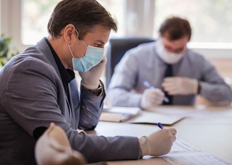 Real estate appraiser conducting a commercial appraisal review assignment while wearing a protective mask