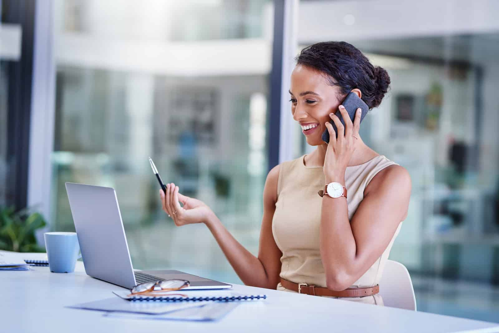 Shot of a young businesswoman using a mobile phone and laptop at her desk in a modern office