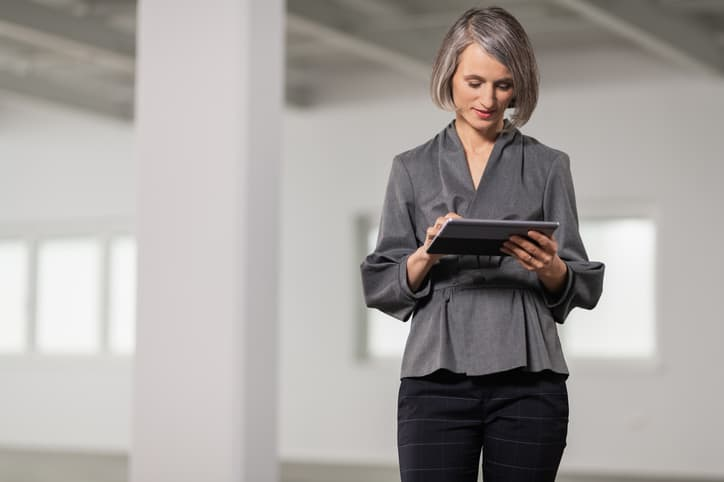 Female appraiser in modern empty office using tablet as appraisal technology tool