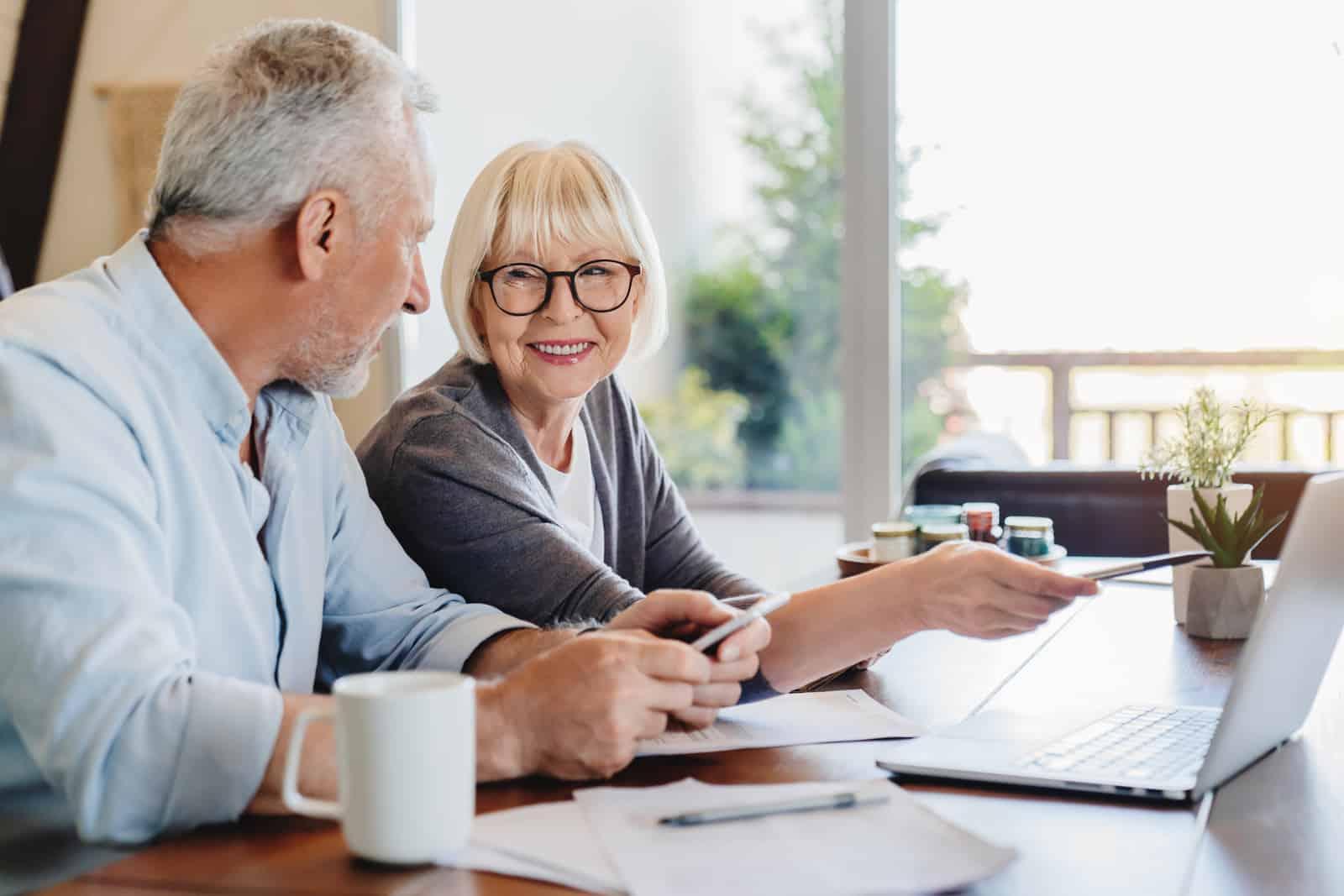 Senior couple doing home finances using laptop indoors