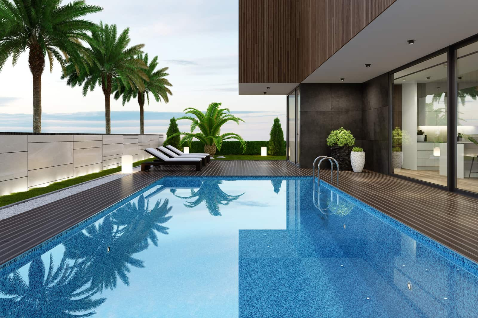 Luxurious beach side villa with swimming pool and palm trees at summer sunset scene